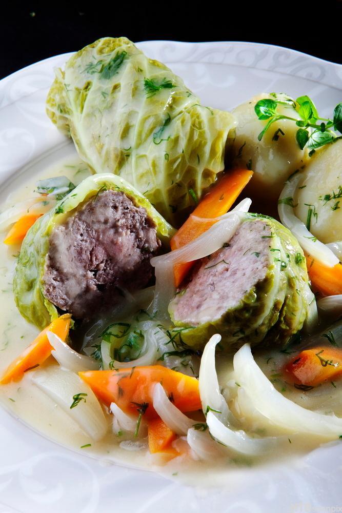 Kålruletter i lys saus med grønnsaker. Foto.