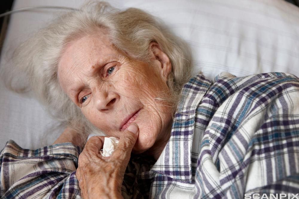 Eldre kvinne som ligger i en seng. Foto.
