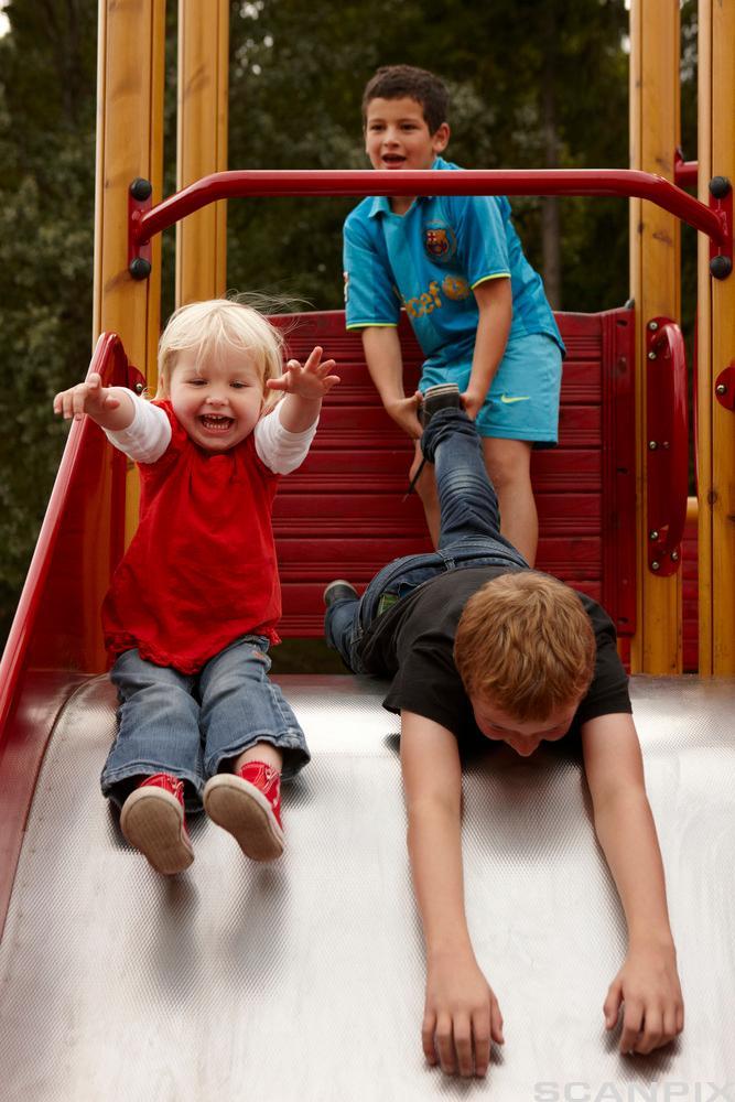 Barn i sklie på lekeplass. Foto.