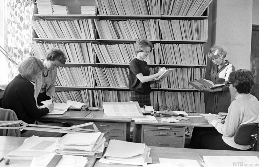 Mennesker fra 70 tallet som leser dokumenter ved siden av en stor bokhylle. Foto
