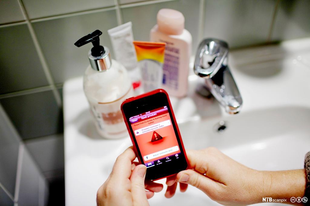 Mobilapp sjekker innhold i kosmetikk som står på en vask. Foto.