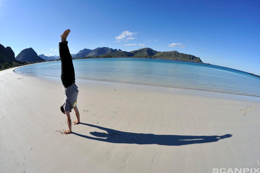 Person som står på hendene på en strand med horisonten bak. Foto.