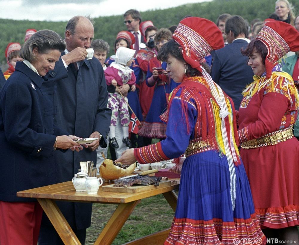 Kong Harald og dronning Sonja blir servert mat ute av to samekvinner. Foto
