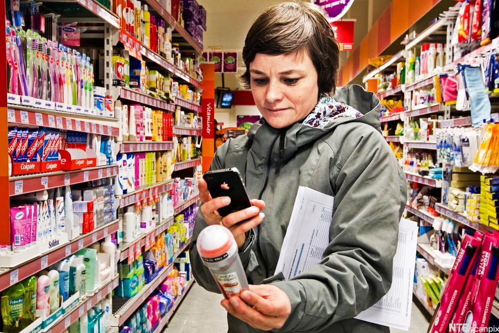 Kvinne står mellom reolene i en butikk, holder en deodorant og tar bilde av varedeklarasjonen på deodoranten med mobilkameraet sitt. Under armen holder hun et skjema. Foto.