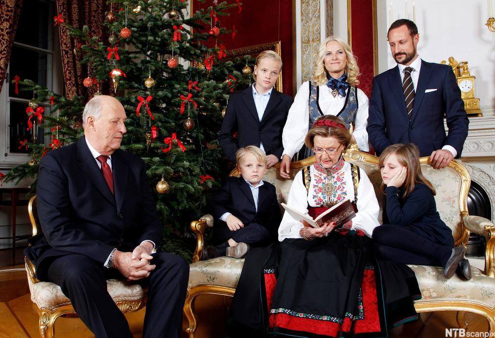 Hele kongefamilien foran juletreet. Sonja leser eventyr for barna.