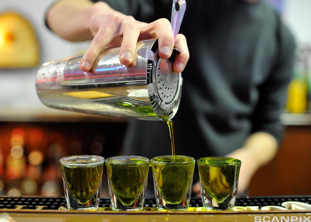 To bartenderar lagar drinkar og tek imot betaling. Foto.