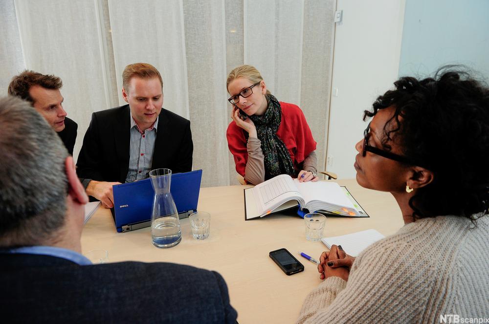 Fem personer sitter i et kontormøte. Foto.