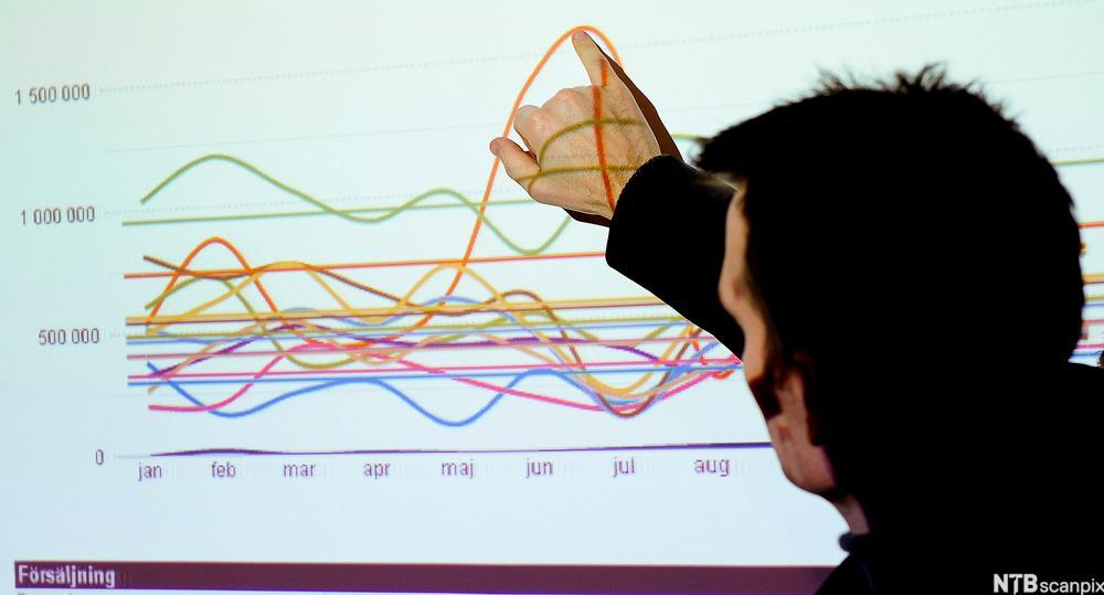 Mann peker og forklarer en graf som er vist med projektor. Foto.