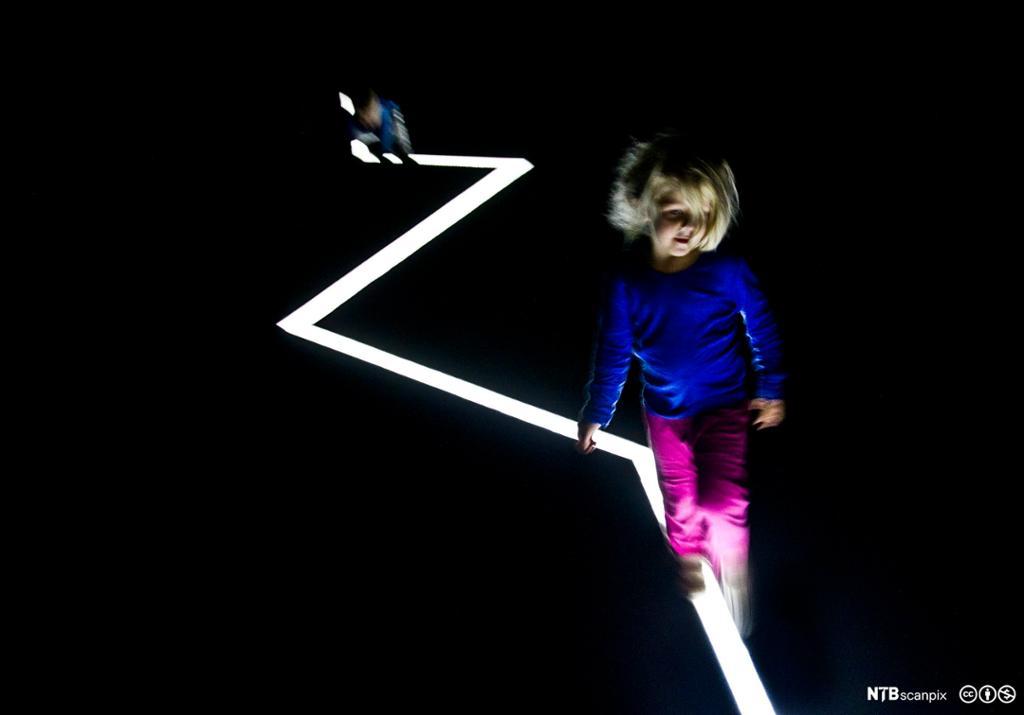 Ei lita jente går langs ei hvit, taggete lysstripe i et helt mørkt rom.