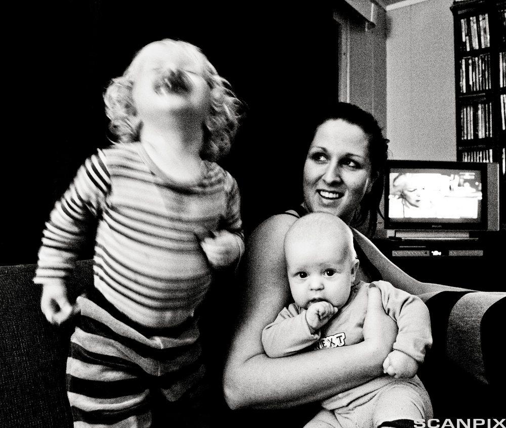 Mor med et lite barn på fanget og et barn ved siden av. Foto.