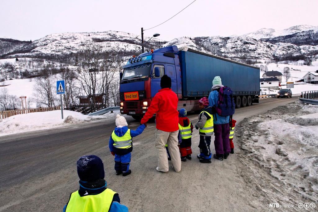 Voksne og barn skal krysse en vei med tungtrafikk. Foto.