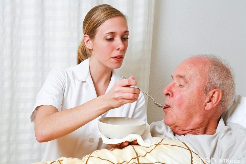 Eldre mann får hjelp med måltidet. Foto