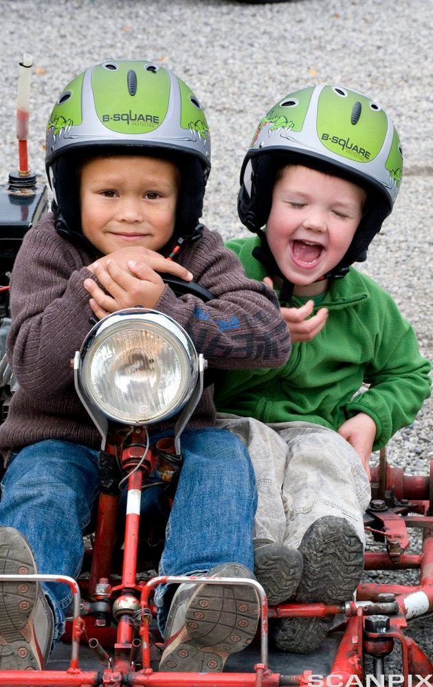 To barn som sitter sammen på en olabil. Foto.