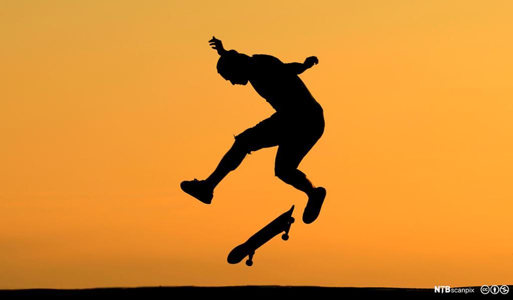 Ung mann gjør triks med skateboard. Foto.