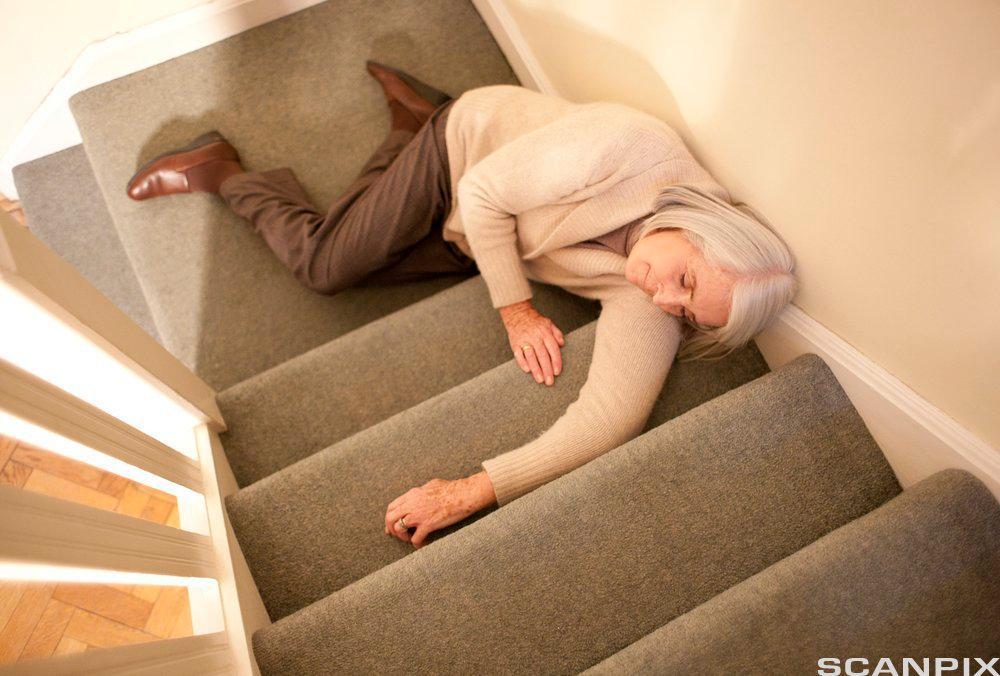 Kvinne ligger livløs i en trapp