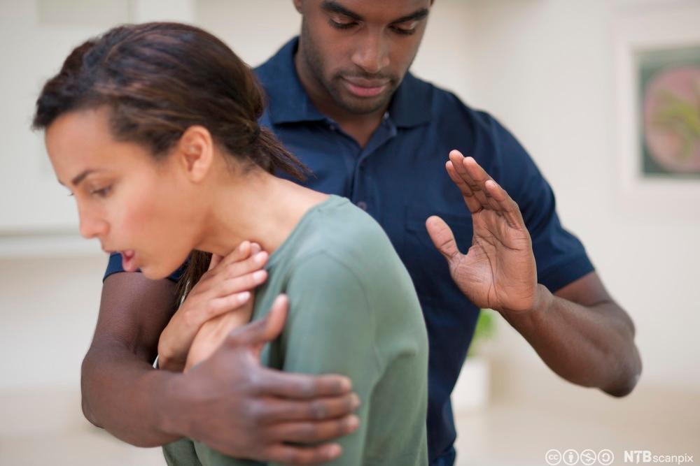Kvinne med fremmedlegeme i halsen. Mann slår i ryggen. Foto.