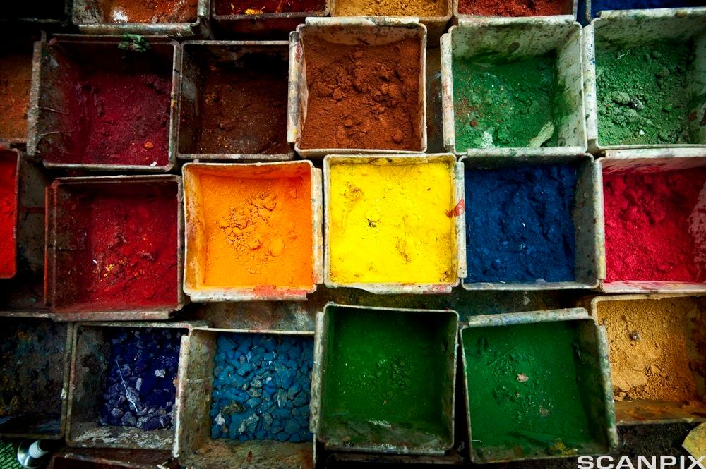 Picture from above of boxes containing different colours in powder form. Foto.