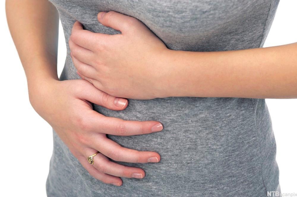 Bilde av en kvinne som holder seg for magen. Foto
