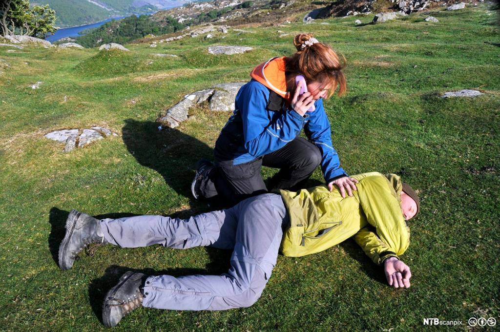 En kvinne utfører førstehjelp på en mann. Foto.