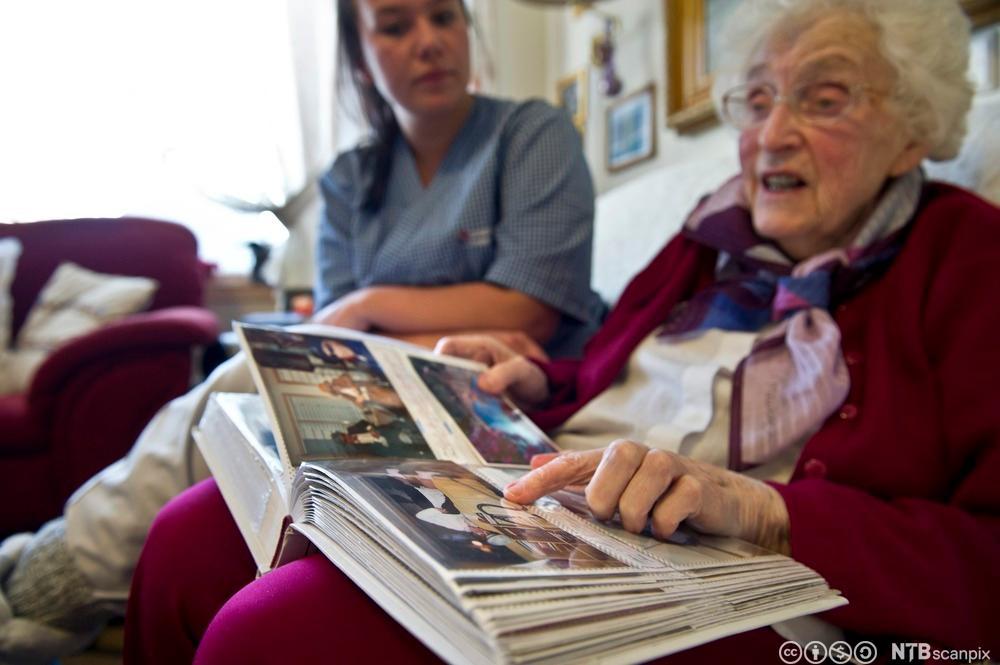Pleier og eldre kvinne ser på fotoalbum sammen. Foto.