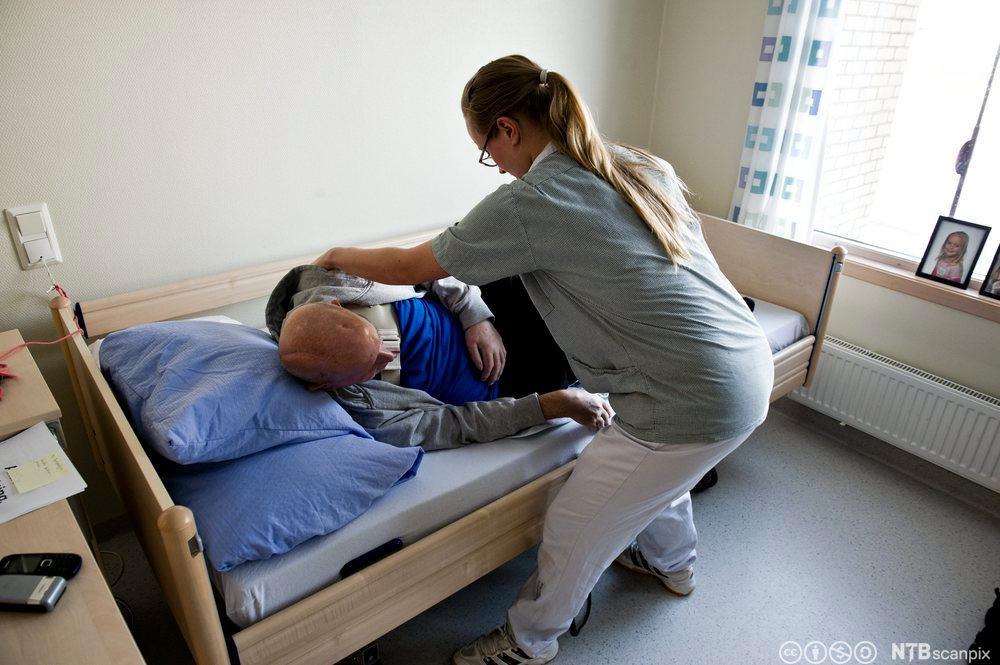 Pleier hjelper slagrammet pasient med å legge seg til rette og snu seg i sengen. Foto.