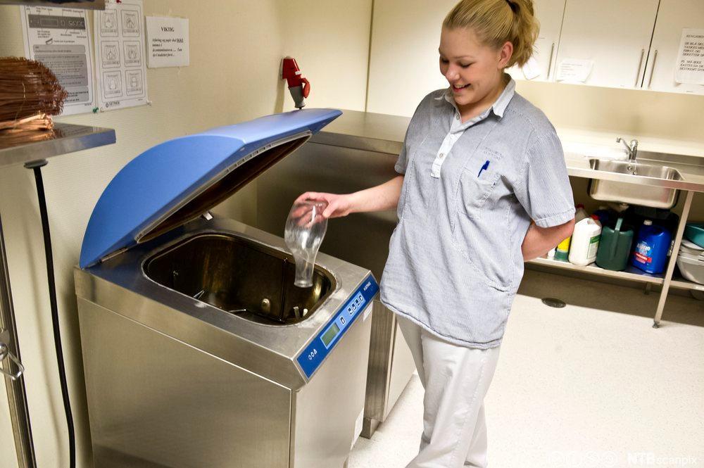 Helsefagarbeider som desinfiserer utstyr på skyllerommet. Foto.