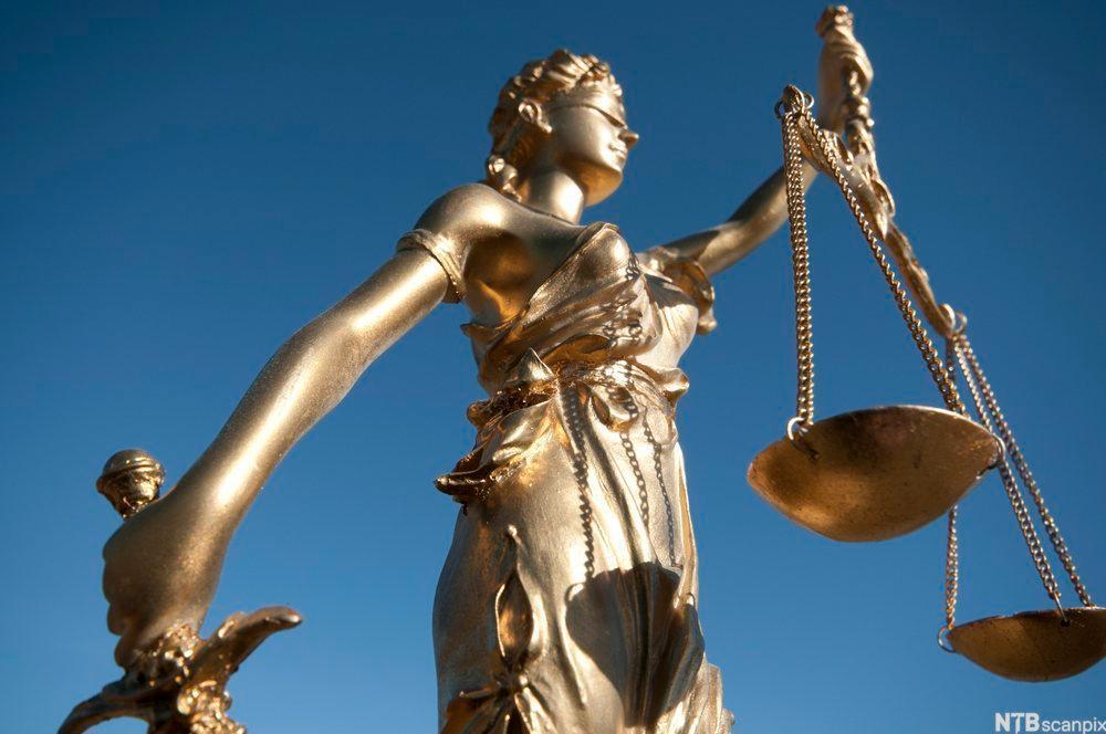 Statue av Justitsia med bind for øynene, sverd i en hånd og vekt med to vektskåler i den andre.. Foto.