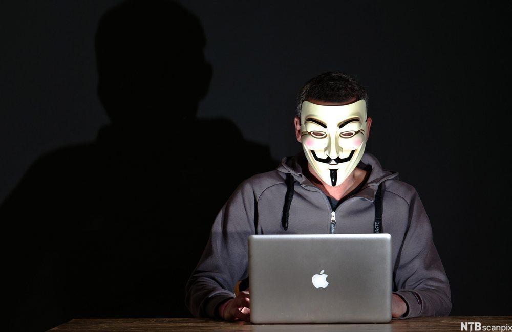 Bilde. Mann med maske foran en dataskjerm.