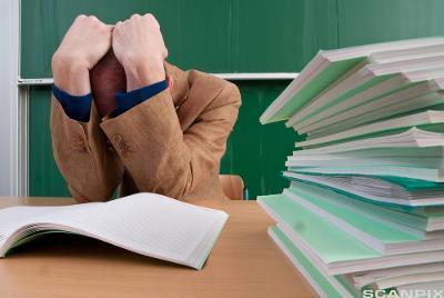 Lærer som sitter bøyd over rettebunke med hodet i hendene. Foto.
