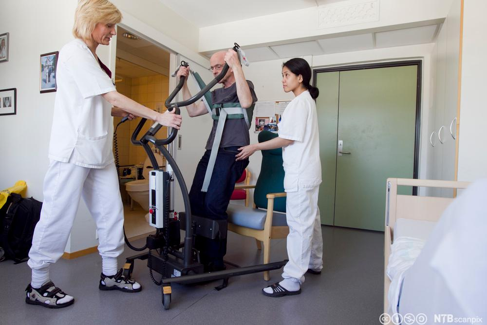 Helsefagarbeidere hjelper en mann med å reise seg fra en stol ved hjelp av et løfteapparat. Foto.