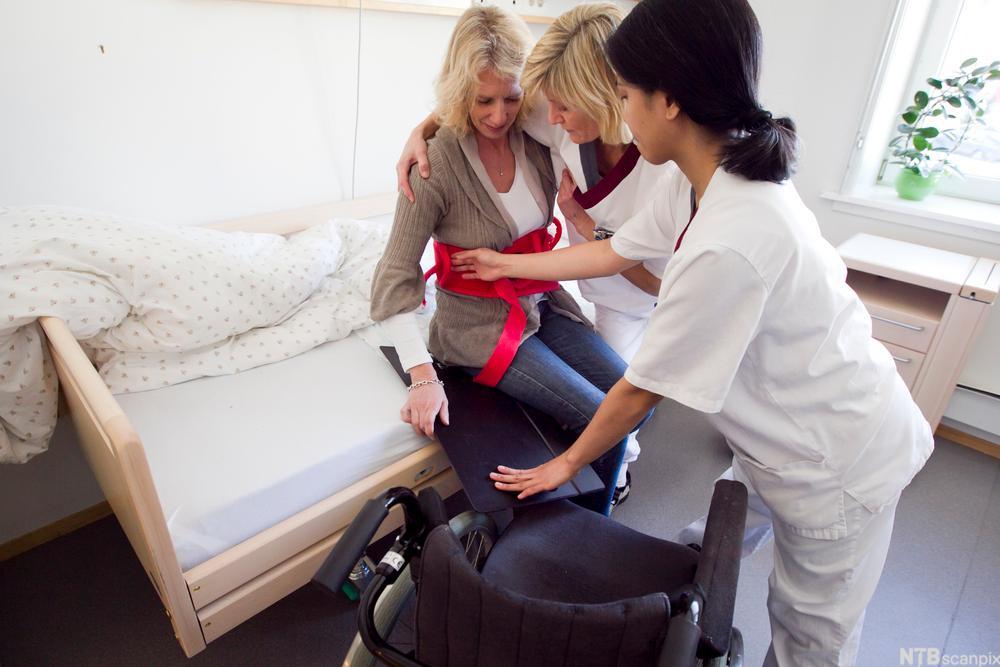 Bildet viser helsefagarbeidere som hjelper en kvinne med å forflyttes fra seng til rullestol