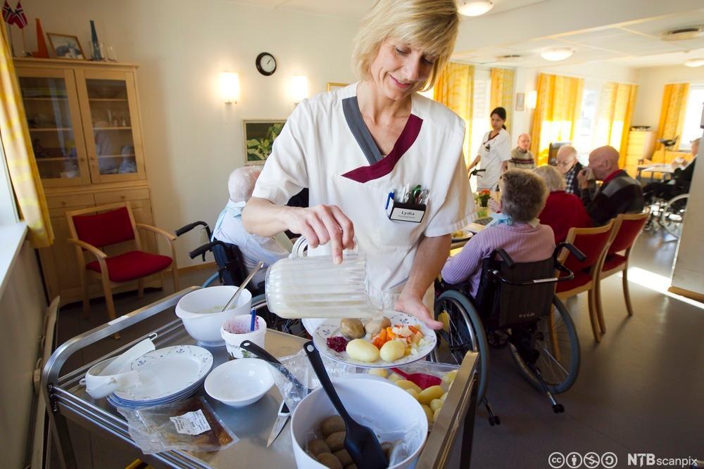 Helsefagarbeider legger på middagsmat på en tallerken. Foto.