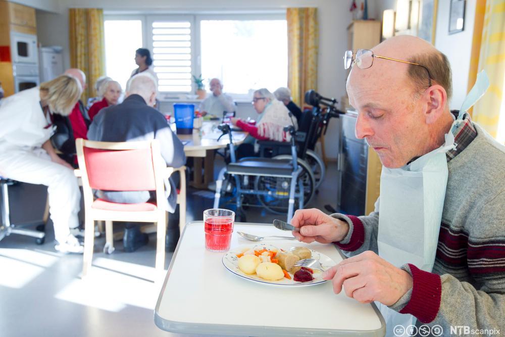 En mann får hjelp til å spise middag av en helsefagarbeider. Foto.