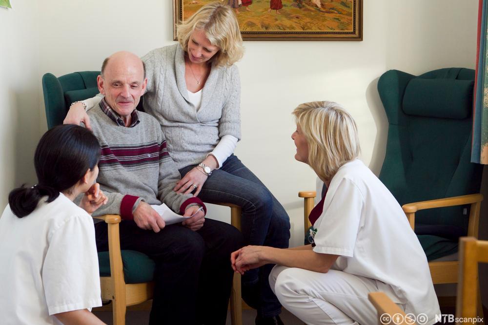 Pasient og pårørende i samtale med helsefagarbeidere. Foto.