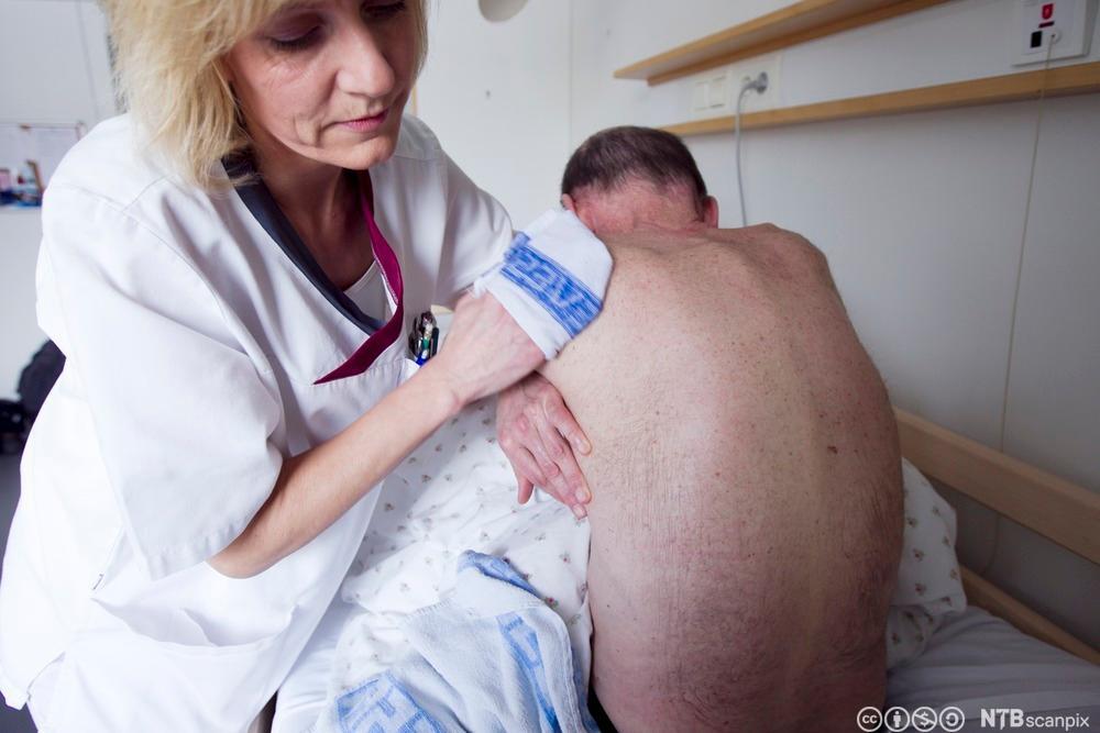 Helsefagarbeider vasker en mannlig pasient. Foto.