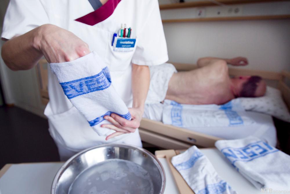 Mannlig pasient i seng, hjelpepleier klargjør vask i seng. foto.