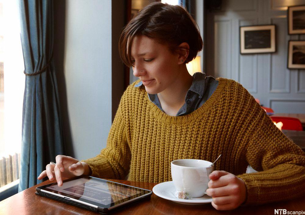 En kvinne sitter ved et bord med nettbrett og en kopp. Foto.