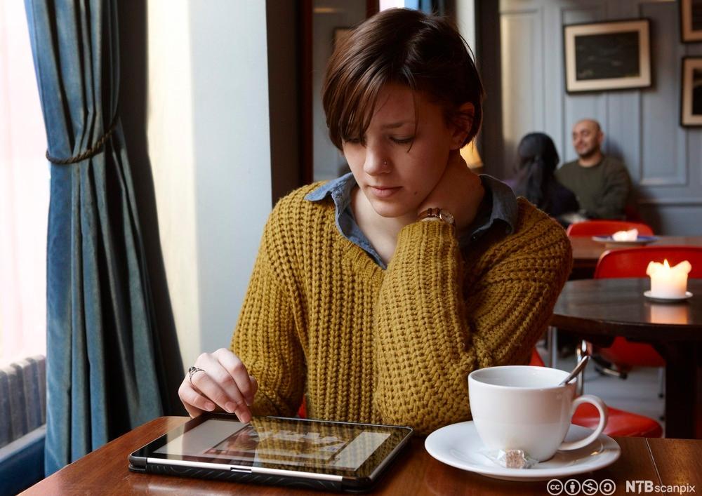 Ung kvinne sitter på kafé og leser nyheter på nettbrett. Foto.
