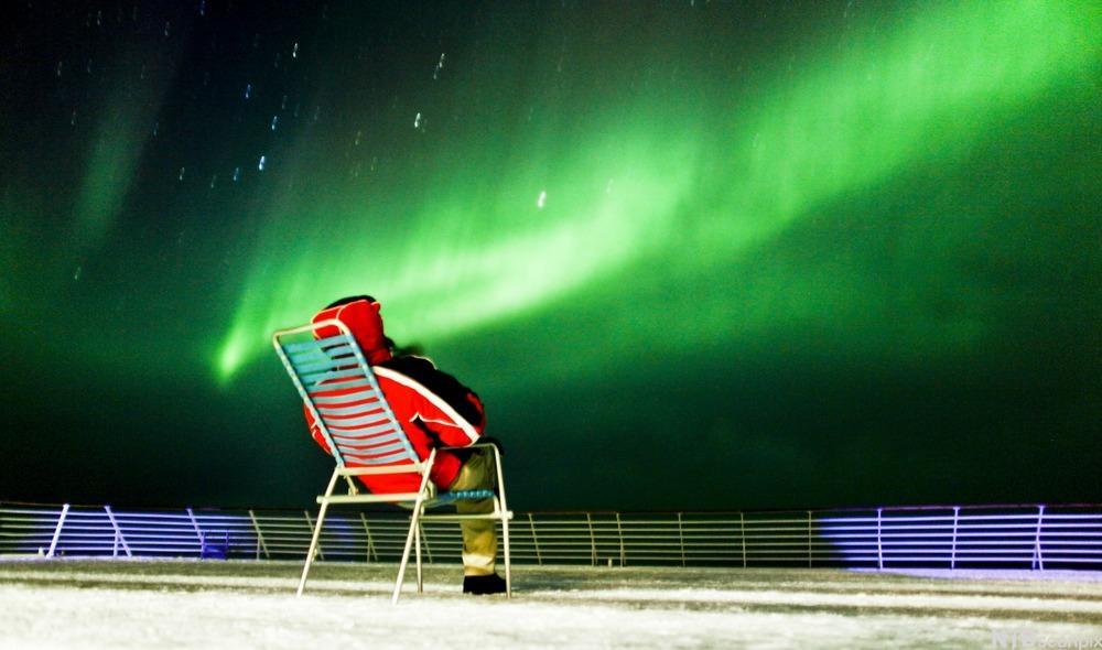 Person sitter i stol på båtdekk og ser på nordlys. Foto.