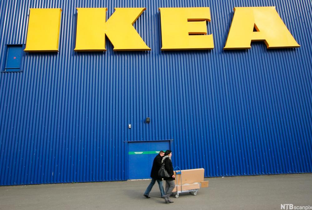Bilde av et par med handlevogn utenfor et IKEA-varehus.