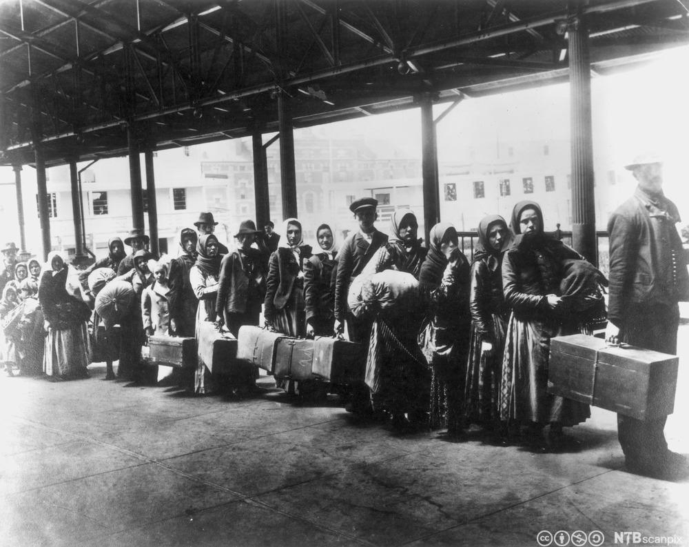 Immigranter står i kø etter ankomst på Ellis Island, ca 1900. Foto.