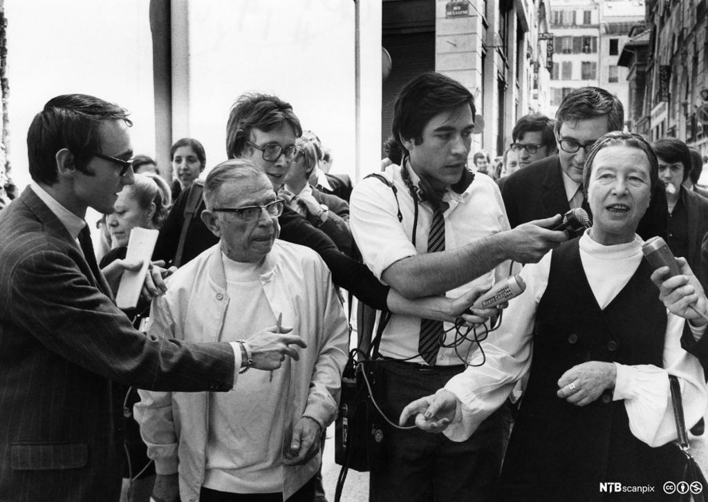 En kvinne og en mann går gjennom en folkemengde og snakker med journalister med mikrofoner. Svart/hvitt-foto.