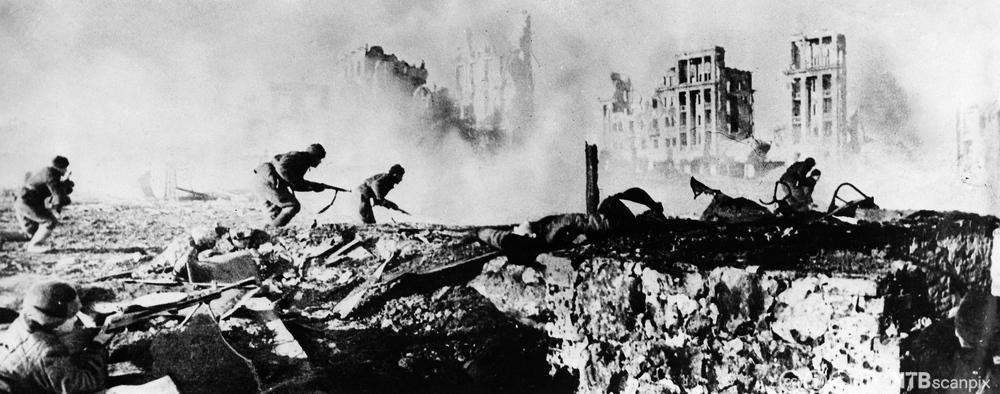 Soldater rykker framover i brennende ruiner i slaget om Stalingrad, 1942. Foto.