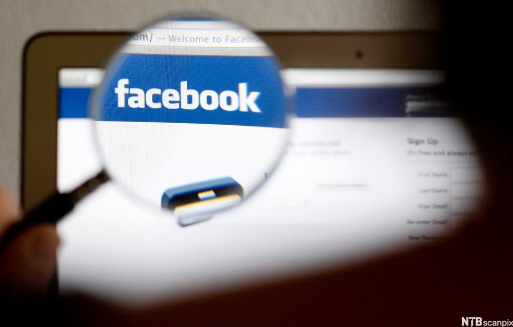 Bilde av et forstørrelsesglass som holdes fremfor Facebook-logoen på en datamaskin