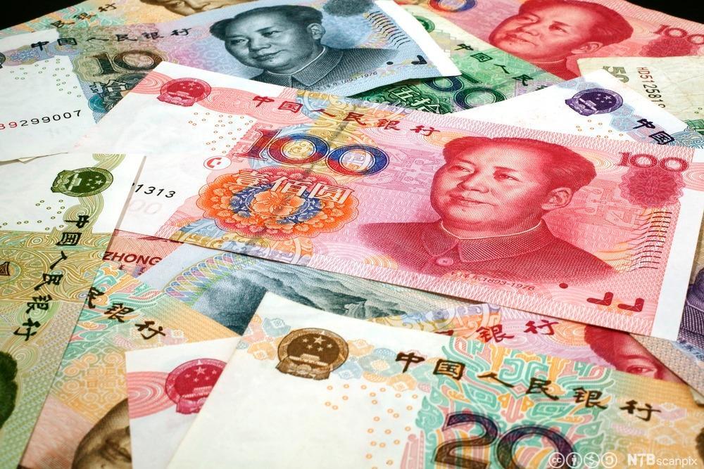 Forskjellige kinesiske pengesedler spredt utover et bord. Foto.