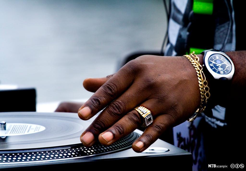 Nærbilde av hånd med gullsmykker som hånterer en lp-plate. Foto.