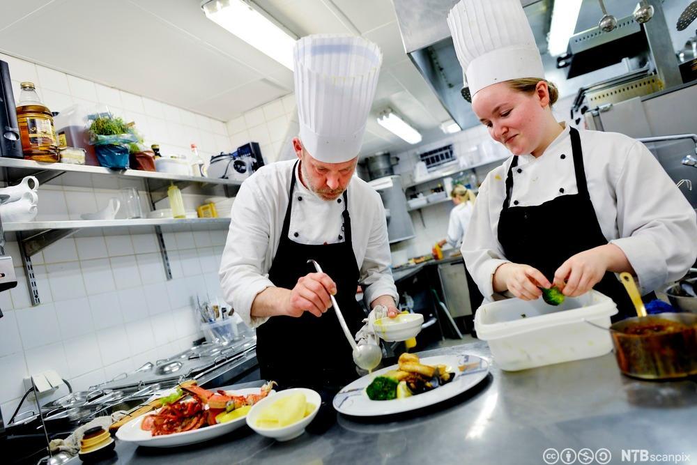 To kokker tilbereder mat ved en benk på et kjøkken. Foto.