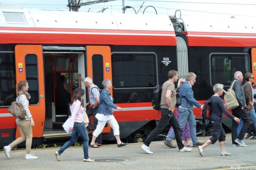Passasjerer foran tog på perrong. foto.