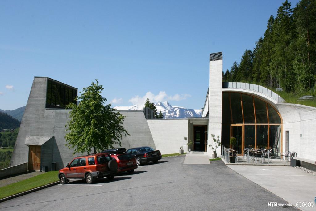 Det nye, moderne museumsbygget på Ivar Aasen-tunet. Snødekte fjell i bakgrunnen, og blå himmel. Foto.