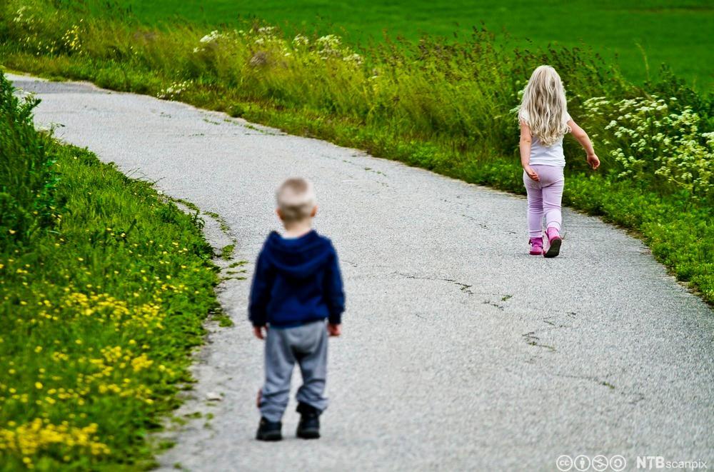 Lita jente som går fra liten gutt. Foto.